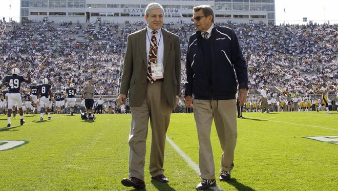 Graham Spanier, left, and head football coach Joe Paterno chat before an NCAA  game against Iowa in State College, Pa., in 2011.