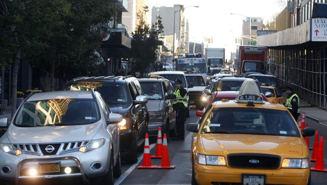 Traffic backs up along the Crescent Street approach to the Queensboro Bridge as police check to ensure that motorists adhere to HOV (High Occupancy Vehicle) restrictions in the aftermath of superstorm Sandy on Thursday.