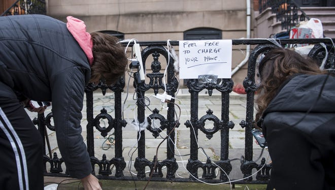 People charge their cell phones outside a home that did not lose power in Hoboken, N.J.