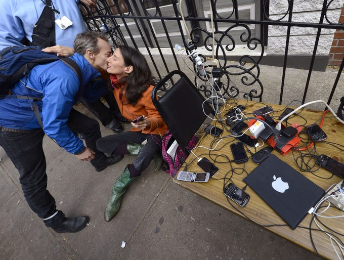 People hug as they wait to have their phones and laptops charged at a portable generator set up on Nov. 1 in the West Village in New York City. Hurricane Sandy left parts of the state and the surrounding area flooded and without power.