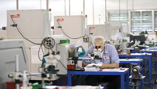 Perica Eldic, employee at Astro Medical Devices in Mentor, OH, using a microscope and a deburring machine to fine tune a small implant device that the company produces.