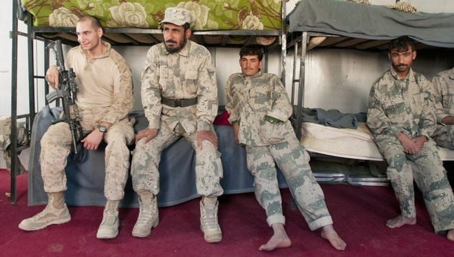 Capt. Greg Schneider (left), meets with Afghan Border Police last month at their headquarters near Taghaz.