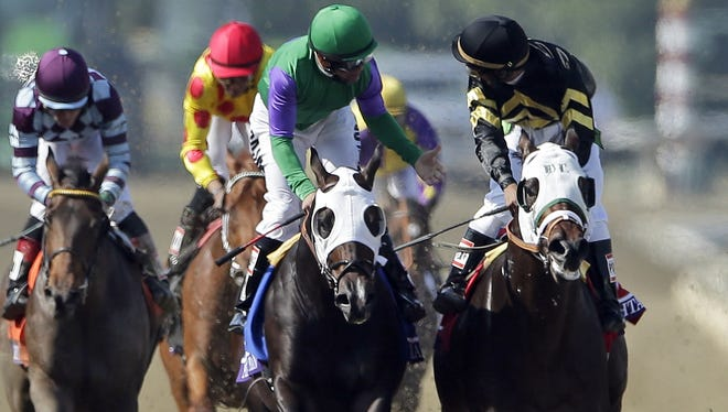 Jockey Patrick Valenzuela, second from right, aboard Merit Man, reacts toward Jockey Rajiv Maragh, aboard Hightail after the pair crossed the finish line in the Juvenile Sprint Friday. Hightail was declared the winner in a photo finish.