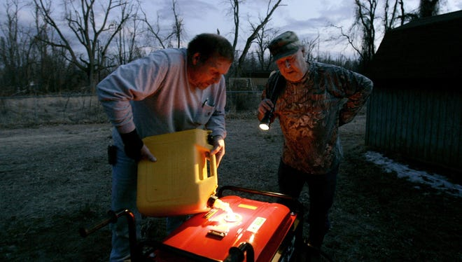 People fill a portable generator with fuel following a winter storm.