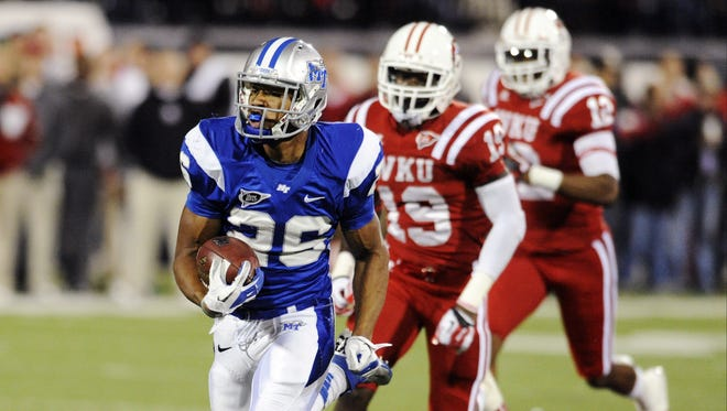 Middle Tennessee running back Jordan Parker (26), racing past Western Kentucky defensive back Cam Thomas (19) and linebacker Tye Golden (12), rushed for 149 yards on 32 carries and scored a touchdown.