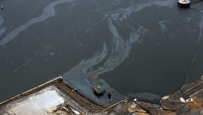 Spilled fuel and pollutants flow Friday in a canal connected to the Arthur Kill major navigation channel for the port of New York and New Jersey.