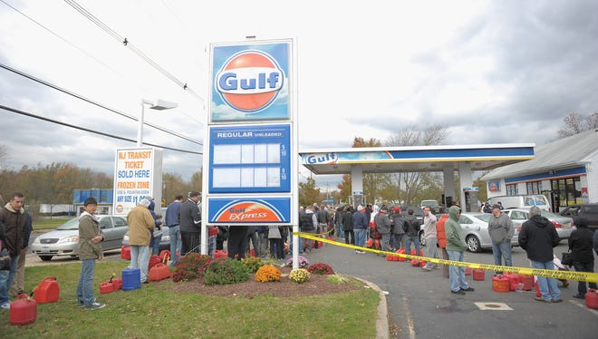 People wait for hours with gas canisters at a Gulf gas station Thursday in Manalapan, N.J.