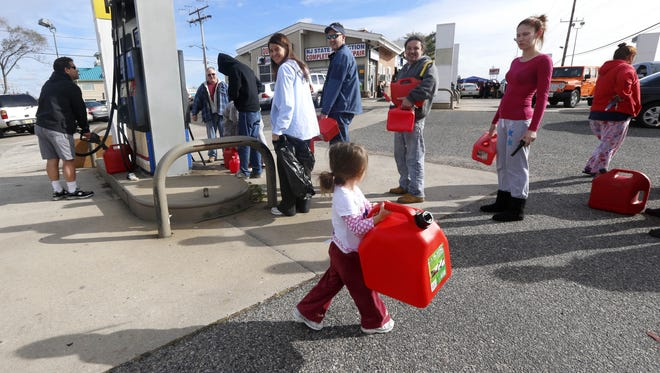 Kora Ferrone, carries a five-gallon gas can Thursday as she helps her father, Chris Ferrone, in line at a station in Toms River, N.J.