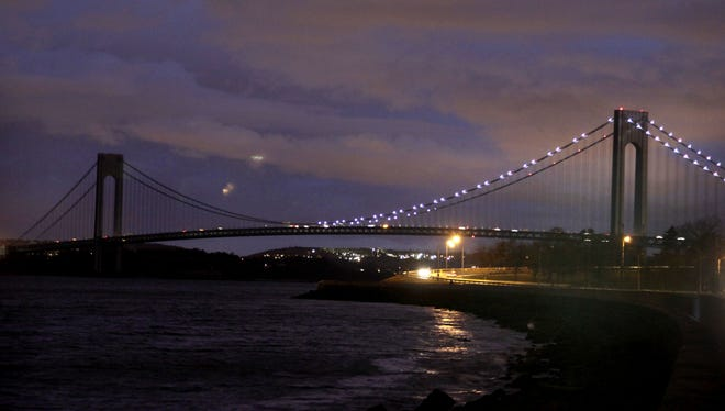 The half of the Verrazano Narrows Bridge attached to Brooklyn is lit while the half attached to Staten Island is dark in New York on Friday night.