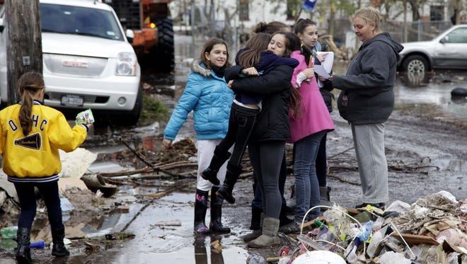 Natalie Arellano, 12, hugs and lifts up Isabella Carvalho, 8, after they met Friday on the street in their neighborhood in Staten Island. The two friends had not seen each other since their families evacuated because of this week's storm.