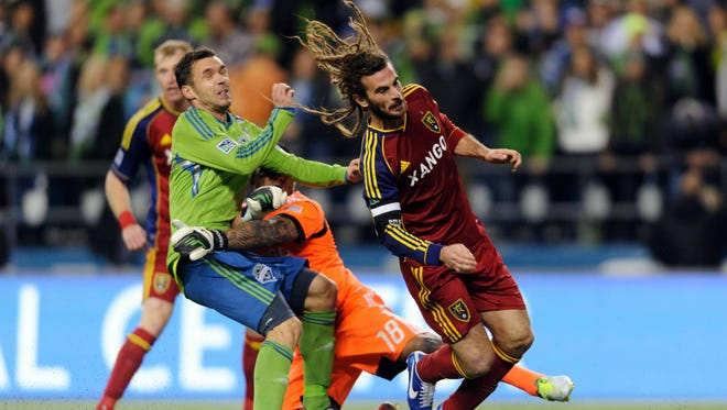 Real Salt Lake goalkeeper Nick Rimando collides with Seattle Sounders FC midfielder Christian Tiffert during the second half of the teams' scoreless draw.