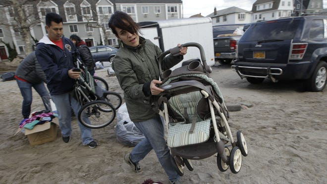 Volunteers carry donated baby strollers in a sand-filled parking lot that was pressed into service in the Rockaways, a neighborhood that was hit hard and is still without power Saturday in New York.