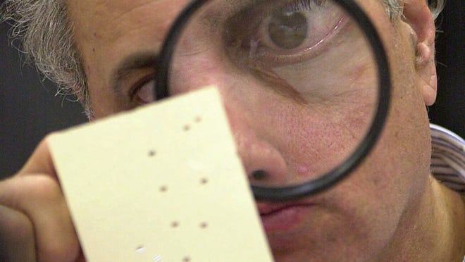 Election official Robert Rosenberg examines a disputed ballot in Broward County, Fla., on Nov. 24, 2000.