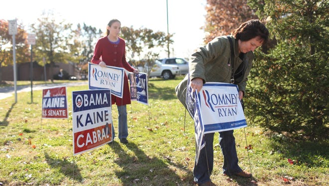 Nina Aldrich, right, and her daughter, Catherine, 23, add signs for Republican candidates in Herndon, Va.