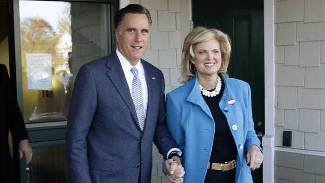 Republican presidential candidate Mitt Romney and his wife Ann Romney emerge after they voted in Belmont, Mass., on Tuesday.