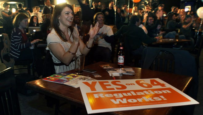 Amanda Jetter celebrates along with others attending an Amendment 64 watch party in Denver.