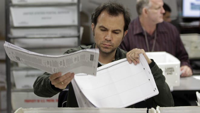 Miami-Dade County elections workers count absentee ballots in Doral, Fla., on Wednesday.
