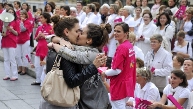 """Two women kiss in front of people taking part in a demonstration called by the """"Alliance VITA"""" association against gay marriage and adoption by same-sex couples on October 23 in Marseille, France."""