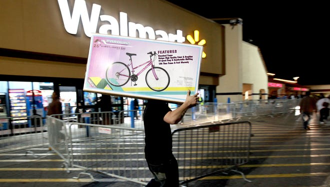 A shopper walks to his car after purchasing a bike at Walmart in Butler Plaza on Thursday, Nov. 24, 2011, in Gainesville, Fla.