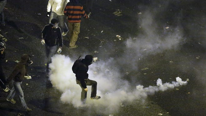 Protesters kick back a tear gas canister towards riot police in front of the parliament during clashes in Athens, Nov. 7.