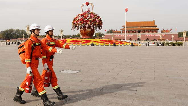 Two firefighter guards march across Tiananmen Square on Wednesday in Beijing.