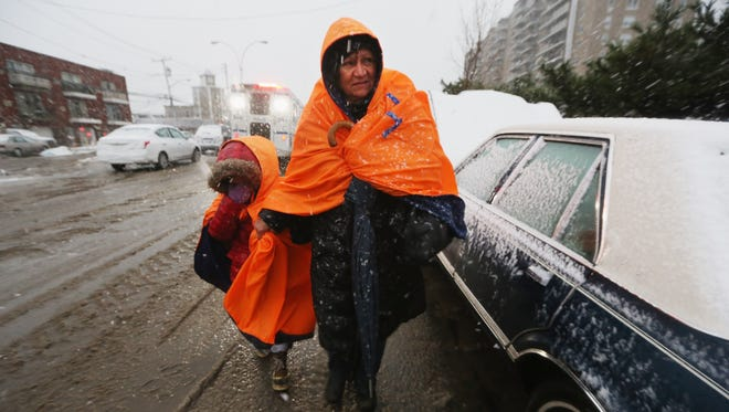 NEW YORK, NY - NOVEMBER 07:  Fatima Quentiro walks with her granddaughter Galalea Castro through the snow to a bus stop to take a bus to Quenitroâ??s home after Castroâ??s home was damaged by flooding as a Norâ??Easter approaches in the Rockaway neighborhood on November 7, 2012 in the Queens borough of New York City. The two are wearing jackets donated by the NYC Marathon. The Rockaway Peninsula was especially hard hit by Superstorm Sandy and some are evacuating ahead of the coming storm.  (Photo by Mario Tama/Getty Images) ORG XMIT: 155912792 ORIG FILE ID: 155719626