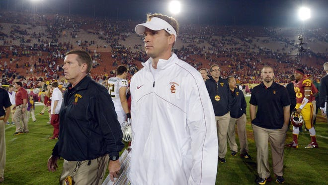 USC coach Lane Kiffin walks off the field after the Trojans' 62-51 loss to Oregon last Saturday, a game that has been marked by scandal after a USC manager admitted to altering game equipment to help the Trojans.