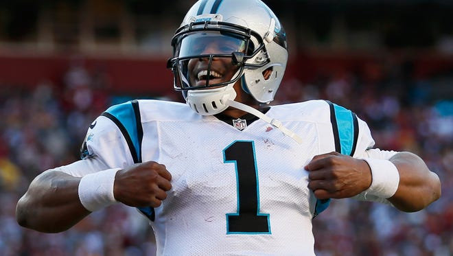 Quarterback Cam Newton of the Carolina Panthers celebrates after rushing for a fourth quarter touchdown against the Washington Redskins at FedExField on November 4, 2012 in Landover, Maryland.