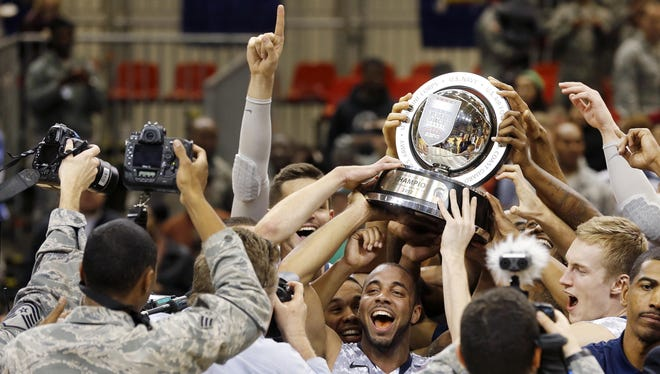 Connecticut guard R.J. Evans, center, holds up the trophy after beating Michigan State in their NCAA men's basketball game on Saturday on the Ramstein U.S. Air Force Base, in Ramstein, Germany.