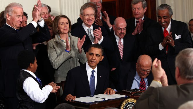 President Obama is applauded after signing the Affordable Health Care for America Act at the White House on March 23, 2010.