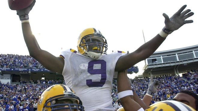 Moments after a catch that carried LSU to victory, teammates carry wide receiver Devery Henderson (9) off the field at Commonwealth Stadium in Lexington, Ky., in Nov. 2002.  LSU won 33-30 when Henderson caught a deflected 75-yard touchdown pass from Marcus Randall as time expired.