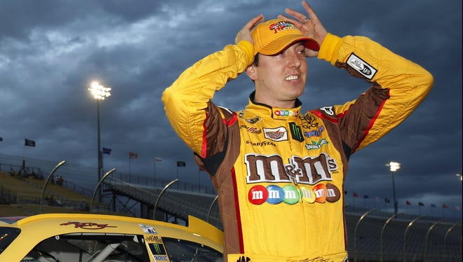 Kyle Busch checks results on a scoreboard after climbing out of his No. 18 car and nabbing the pole position during qualifying for the Sprint Cup Series race at Phoenix International Raceway.