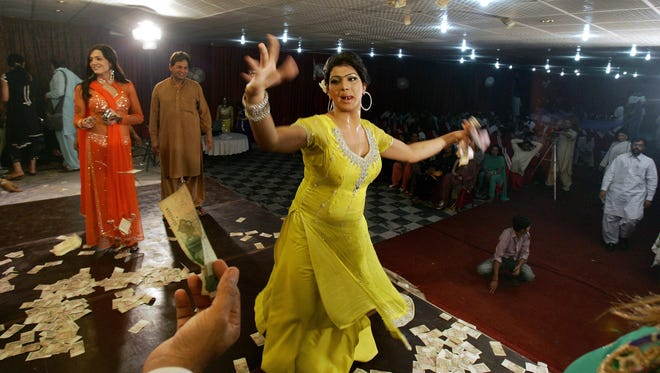 A man, bottom left, offers money to Sonia, 26, a transgender Pakistani, while dancing at the birthday party of her transgender friend, Sana, not pictured, in Rawalpindi, Pakistan.