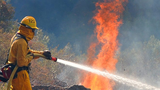 A firefighter battles a blaze in the Painted Cave area of Santa Barbara, Calif., last month.