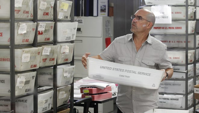 A worker prepares boxes of absentee ballots to be scanned at the Miami-Dade County Elections Department on Tuesday in Doral, Fla.
