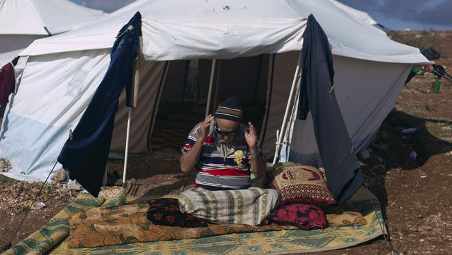 A elderly, disabled man who fled from the violence in his Syrian village, prays in front of his tent at a displaced camp in Atma, Syria, on Saturday.