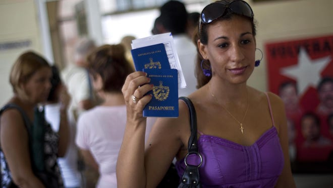 A woman displays her passport and that of her son as she leaves an immigration office in Havana last month.