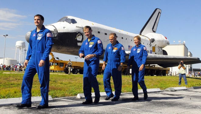 Astronauts, from left, Rex Walheim, Chris Ferguson, Doug Hurley and Sandy Magnus walk alongside shuttle Atlantis as it rolls to the Vehicle Assembly Building at the Kennedy Space Center on May 17, 2011.