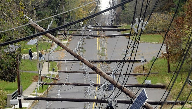 Downed utility poles and wires lie along Bull Run Road in Hopewell Township, N.J., three days after Superstorm Sandy swept through the region.