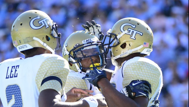 Georgia Tech's David Sims (center) celebrates one of the Yellow Jackets' nine touchdowns with teammates Saturday in a record-setting win at North Carolina.