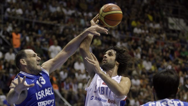 Serbia's Milos Teodosic, right, passes over Israel's Ido Kozikaro, left, in a Group A FIBA EuroBasket 2013 qualifying match in Belgrade, Serbia, Tuesday, Sept. 11, 2012.