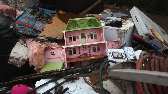 A doll house lies in a garbage heap outside a flood-damaged home on Staten Island/