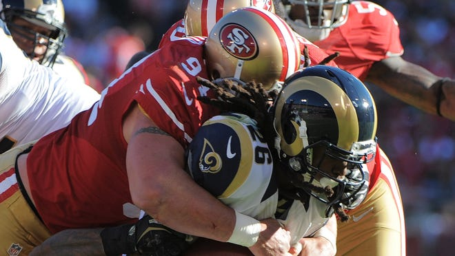 Rams running back Daryl Richardson (26) is tackled by 49ers defensive end Justin Smith (94) during the second quarter at Candlestick Park.