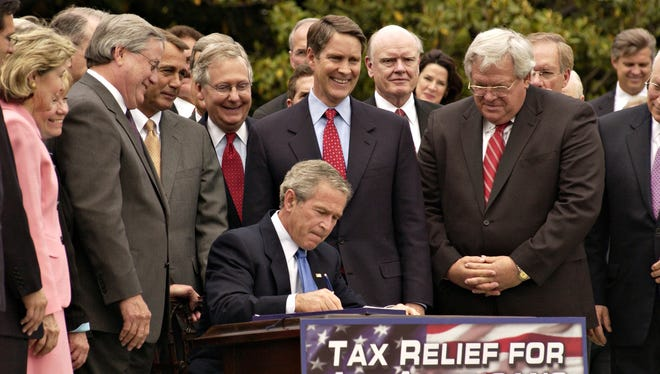 President George W. Bush, surrounded by members of Congress signs the Tax Relief Extension Reconciliation Act of 2005 at the White House on May 17, 2006.