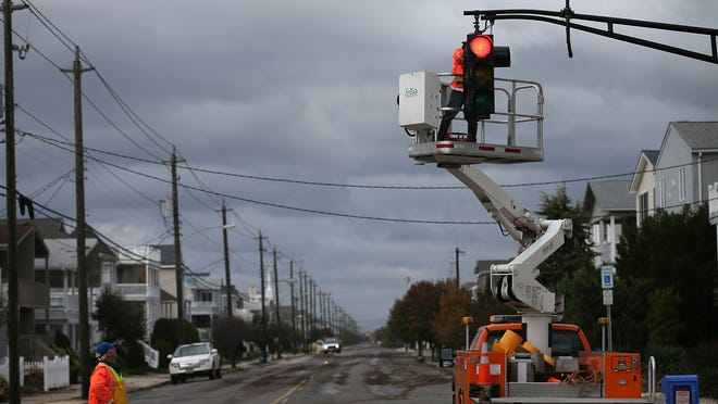 Utility workers repair a stop light damaged by Sandy on Oct. 30 in Ocean City, N.J.