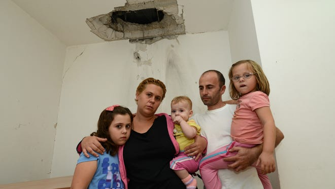 Lital and Doron Ben-Oved pose with their children under the hole in their ceiling made by a rocket fired from Gaza into Kibbutz Kfar Aza, Israel. The children, from left, are Hadar, 8, Zohar, 1,  and Adi, 6,