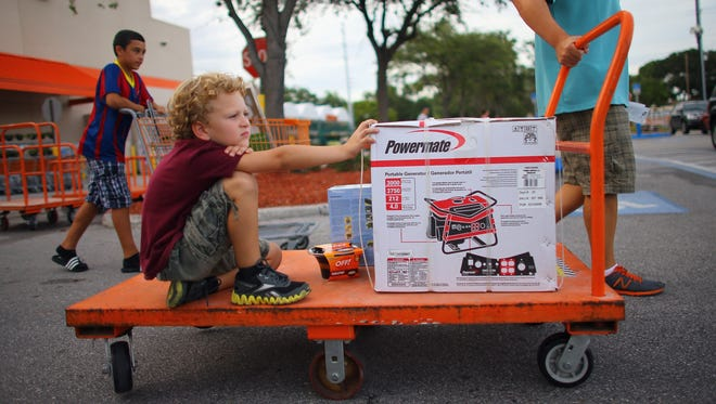 Gideon Campbell rides a cart as his father, Scott, wheels a new generator from Home Depot to their car Aug. 25, 2012 in Tampa, Fla.