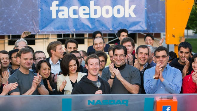 Facebook CEO Mark Zuckerberg (center) is flanked by  employees  as he rings the Nasdaq's opening bell from Facebook headquarters in Menlo Park, Calif., on the company's first day of trading on May 18, 2012.
