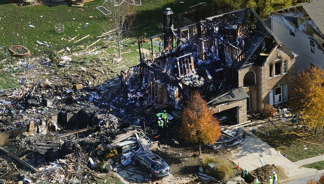 Citizens Energy workers continue their investigation Monday, at the site of an explosion at a house in Indianapolis.