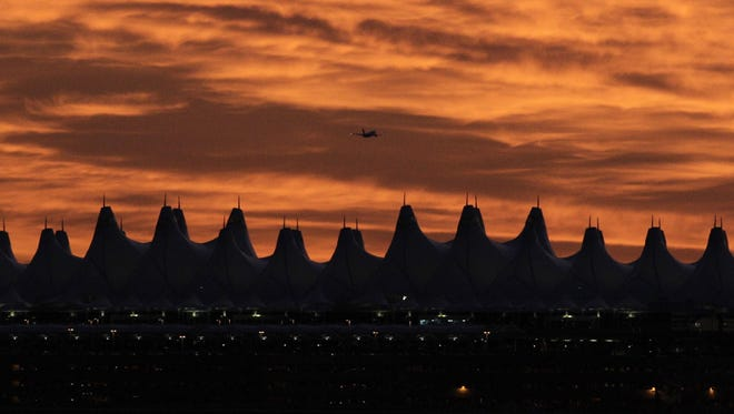 A plane takes off from Denver International Airport at sunrise, Sept. 12, 2010.